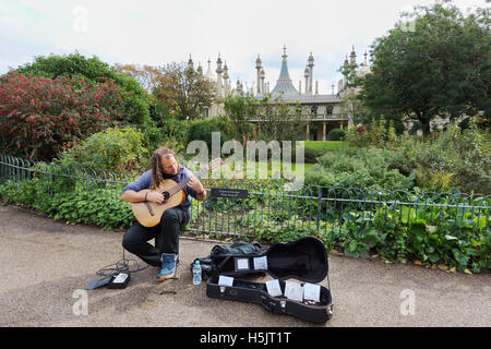 A busker playing guitar in front of the Brighton Royal Pavilion, Brighton, East Sussex England UK - Stock Photo