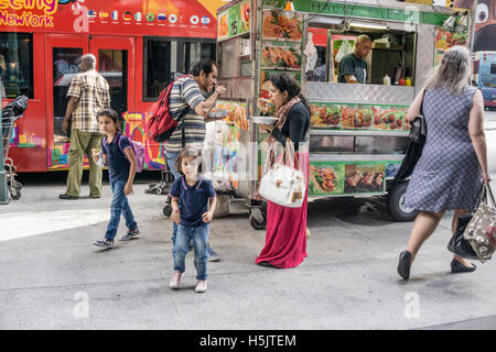 muslim couple stand on 14th street hastily eating plates of Halal food from nearby cart as 2 small daughters start - Stock Photo