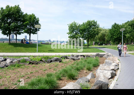 Riverside park is inviting prospect on glorious sunny July 4 4th with people strolling sunning or picnicking with - Stock Photo