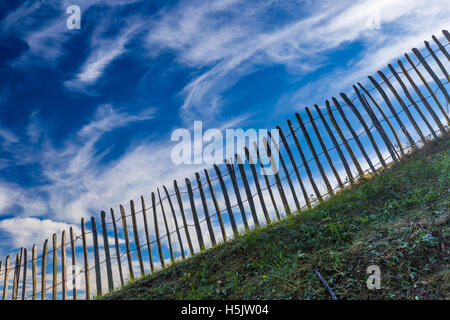 Old wooden fence on dramatic blue sky background - Stock Photo