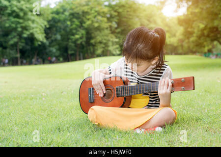 Asian little kids girl sitting on grass and play ukulele in park. Kids funny playing ukulele - Stock Photo