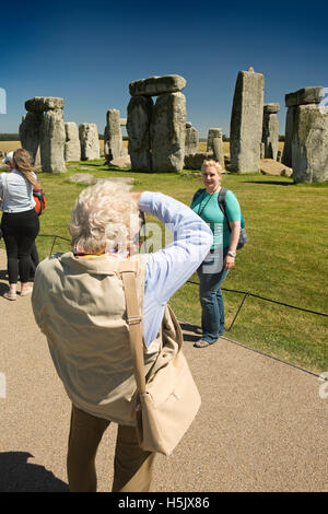 UK, England, Wiltshire, Stonehenge visitors taking souvenir pictures at stones - Stock Photo