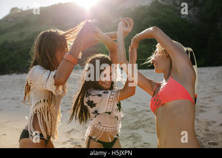 Happy female friends dancing on the beach and having fun. Happy young women enjoying a summer day in sea shore. - Stock Photo
