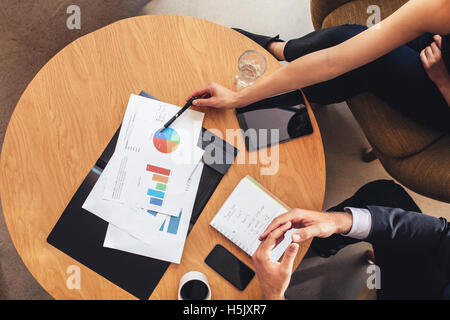 Top view of two business people working with charts around table. Businessman and woman going through business projections - Stock Photo