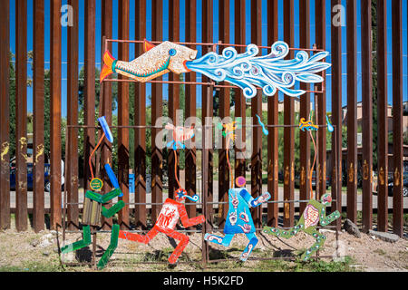 Nogales Mexico - Artwork on the Mexican side of the U.S.-Mexico border fence shows a U.S. Border Patrol agent chasing - Stock Photo