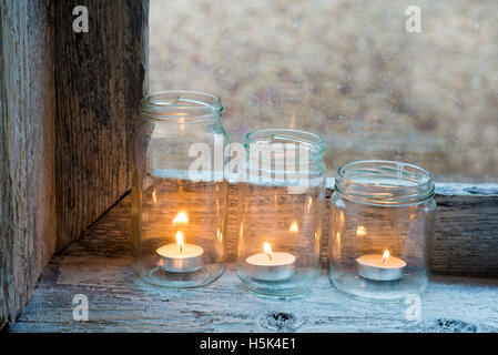 candles in three glass jars on a window sill - Stock Photo