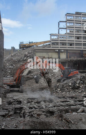 Heavy plant machinery wrecking and breaking up buildings on an inner city demolition site that looks like a war - Stock Photo