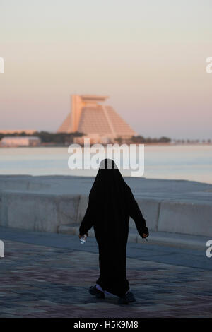 Arab woman wearing a traditional black robe, walking along the Corniche, Sheraton Hotel in the back, West Bay District, - Stock Photo