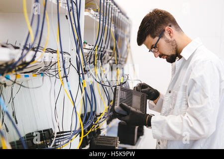 Network technician testing modems in factory - Stock Photo