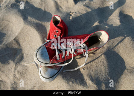 Red Converse 'Chucks', sneakers in the sand - Stock Photo