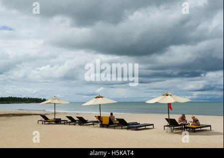 Tourists sitting on a sandy beach in front of one of the resorts in Passikudah Bay, Sri Lanka - Stock Photo