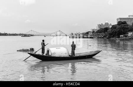 Two men cross Hooghly river in small wooden boat with view of old Howrah bridge on a calm morning after monsoon - Stock Photo
