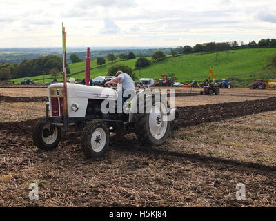 Farmer ploughing with rolling Derbyshire countryside in background. Ashover Ploughing Match, Highoredish Farm, Derbyshire. - Stock Photo