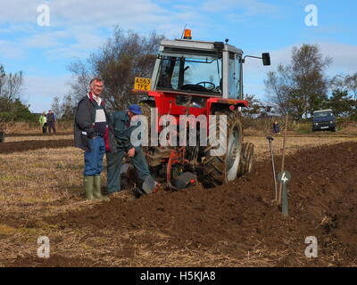 Competitors inspect the ploughing at Ashover Ploughing Match, held at Highoredish Farm, Derbyshire. - Stock Photo