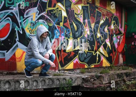 man in hoody draw graffiti - Stock Photo