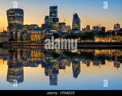 Illuminated London cityscape at sunset with reflection from river Thames - Stock Photo