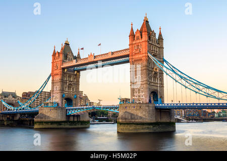Tower Bridge in London at sunset, casting a orange light on part of the bridge - Stock Photo