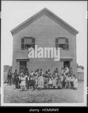 Photograph of the Lincolnville Beach schoolhouse circa 1882.   Children are lined up in front of the school and - Stock Photo