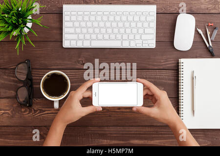 hand holding phone horizontal showing phone blank screen on work table, mock up phone rose gold color - Stock Photo