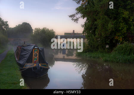 Moored narrowboat and a pretty cottage on the banks of the Moss Hall Winding Hole, Shropshire Union Canal, Audlem, - Stock Photo