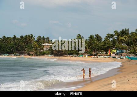 Women on the beach with fishing boats, Arugam Bay, Sri Lanka - Stock Photo