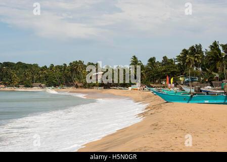 Fishing boats lying on the beach, Arugam Bay, Sri Lanka - Stock Photo