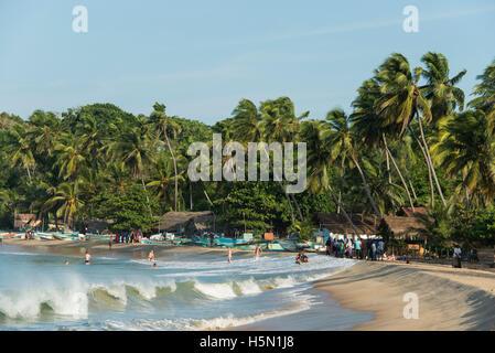 People swimming and on the beach, Arugam Bay, Sri Lanka - Stock Photo