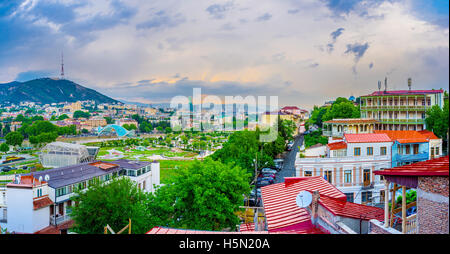 Waiting for the sunset on the top of the hill with the view on the city roofs, Rike Park and beautiful cloudy sky, - Stock Photo