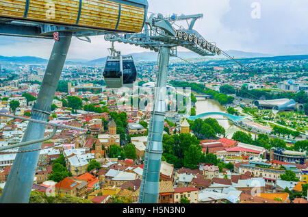 The view on the red city roofs with the constructions of the cableway, located on Sololaki Hill, Tbilisi, Georgia. - Stock Photo