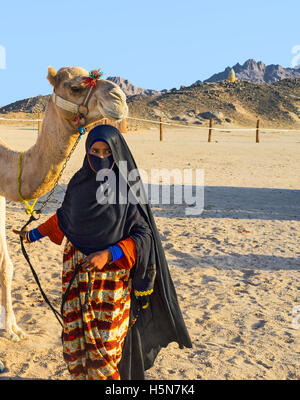 The young girl-cameleer from Bedouin village in Sahara desert with her camel, Hurghada, Egypt. - Stock Photo