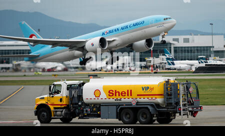 Shell aviation fuel tanker truck Vancouver International Airport Korean Air Cargo Boeing 777F HL8075 airport action - Stock Photo