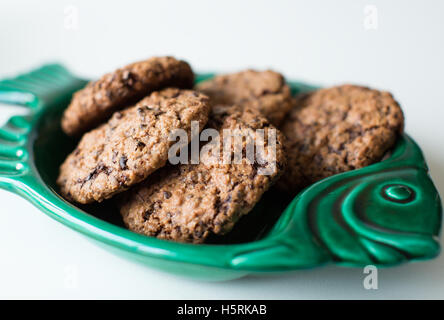 Some tasty fresh baked cookies on a green fish plate - Stock Photo