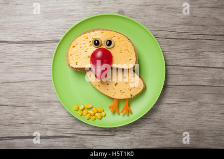 Amusing chicken made of bread and cheese on plate and desk - Stock Photo