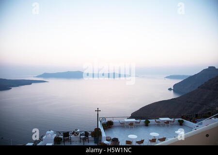 A view over the sea and some islands and a cross on a patio in the sunset - Stock Photo