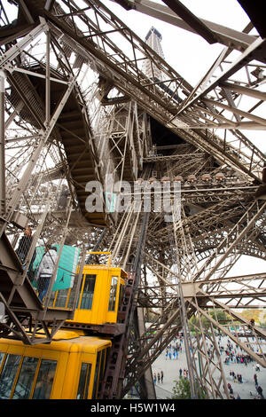 A look from the below of the elevator going up in the Paris tower - Stock Photo