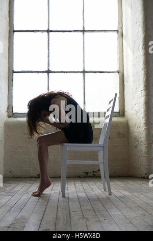 Stressed woman sitting on a chair head in hands crying - Stock Photo