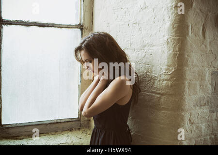 Sad young woman standing near the window hands on neck - Stock Photo