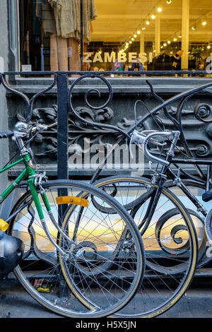 Bicycles against iron railing outside Zambesi clothing store in Flinders Lane, Melbourne, Victoria, Australia - Stock Photo