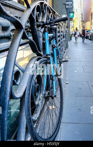 Bicycles against iron railing in Flinders Lane, Melbourne, Victoria, Australia - Stock Photo