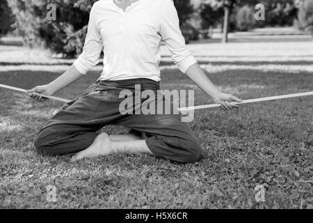 portrait of man sitting on slackline and  balancing on a rope - Stock Photo
