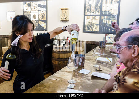 St. Saint Augustine Florida San Sebastian Winery inside wine tasting event woman man Hispanic pouring hostess - Stock Photo