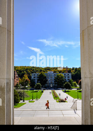 Abstract view of a solitary woman and her child seen walking past a New England State House entrance. - Stock Photo
