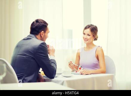 smiling couple eating dessert at restaurant - Stock Photo