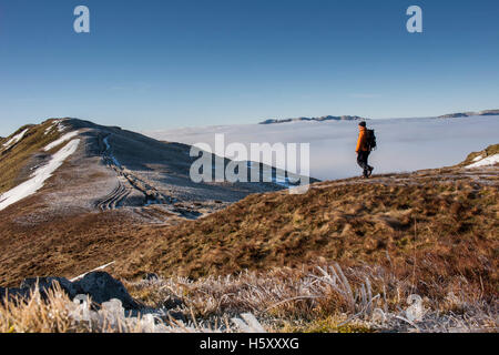 Mountaineer walks towards Heron Pike on the Fairfield Horseshoe above a temperature inversion in the Lake District, - Stock Photo