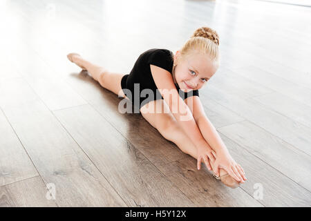 Smiling beautiful little girl ballerina doing twine in ballet studio - Stock Photo