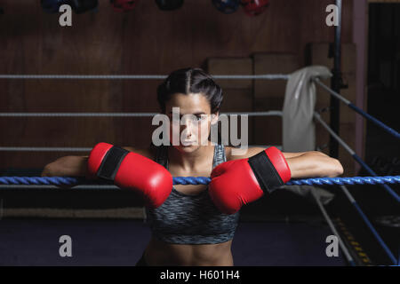 Tired female boxer in boxing gloves - Stock Photo