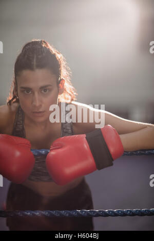 Portrait of female boxer in boxing gloves - Stock Photo