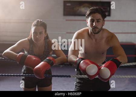 Portrait of male and female boxer leaning on rope - Stock Photo