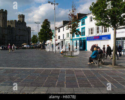View across Castle Square pedstrianised town centre  to Caernarfon Castle Gwynedd North Wales Caernarfon is a  royal - Stock Photo