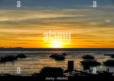 Colorful sunset from the shore of Lake Titicaca in Copacabana, Peru - Stock Photo